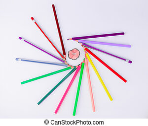 Bunch of crayons and pencils circling a pencil shaving in an isolated white background
