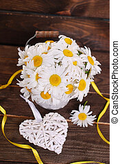 bunch of beautiful fresh daisies in bucket and wicker heart on wooden background
