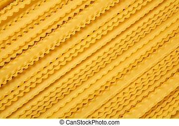 bunch of dry mafaldine pasta on a cane tablecloth