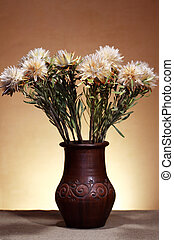 Bunch of flowers in vase against nice brown wall with spot of light