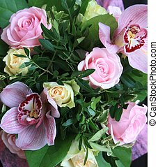 Close up of pink and yellow roses and orchids
