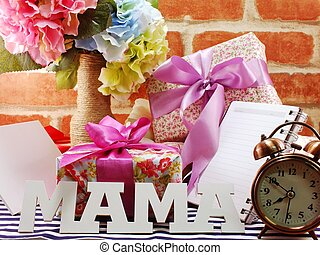 bunch of flowers with a gift box and word mama on wooden background
