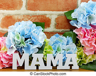 bunch of flowers with a gift box and word mama on wooden...