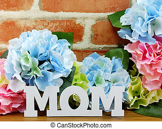 bunch of flowers with a gift box and word mom on wooden background