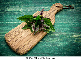 bunch of fresh organic basil in olive cutting board on rustic wooden background