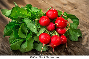 Bunch of fresh red radishes on a wooden table