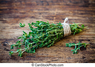 bunch of fresh thyme on a wooden background - bunch of fresh...