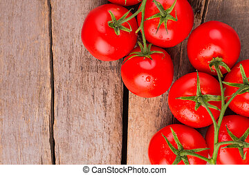 Bunch of fresh tomatoes with water drops on wooden table.