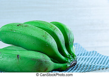 Bunch of freshly picked and still green bananas on a flat surface
