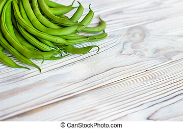 Bunch of freshly picked green beans on a wooden table surface.