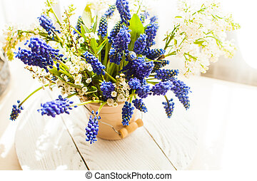 Bunch of grape hyacinths in a ceramic vase