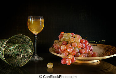 bunch of grapes lying on round wooden plate next to glass white wine standing background with reflection