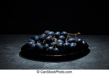 bunch of grapes on a plate black grapes