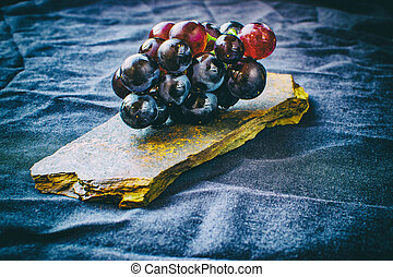 Bunch of grapes on a stone with a cloth background.