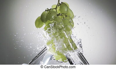 bunch of green grapes in a spray of water