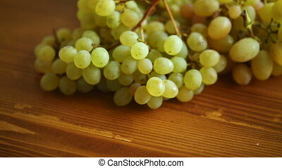 bunch of green grapes on a dark wooden table close-up