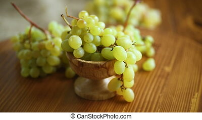 bunch of green grapes on a dark wooden table