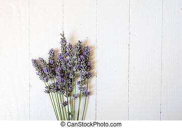 Bunch of lavender flowers lying on a white wooden background