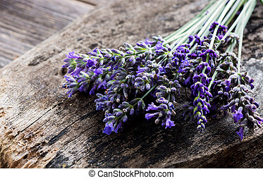 Bunch of lavender flowers on a wooden background.