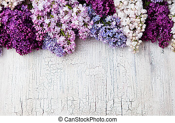 Bunch of lilac flowers on a crackling wooden background Top view copy space
