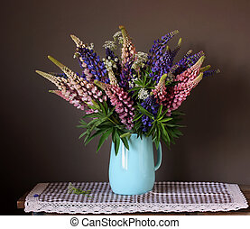 Bunch of lupins. Still life with garden flowers in a jug.