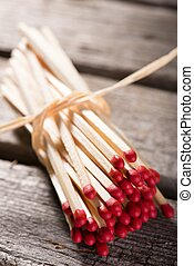 Bunch of matchsticks bonded by piece of straw
