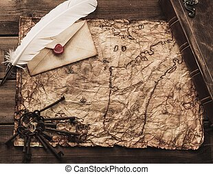 Bunch of old keys, book and envelope on a vintage map