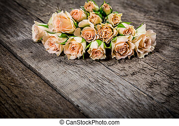 Bunch of pastel roses on wood background