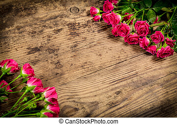 Bunch of pink roses on wood background