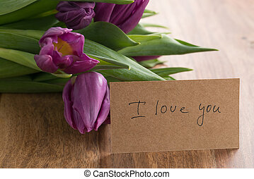 bunch of purple tulips on wood table with i love you card