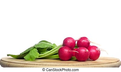 Bunch of radishes are spinning on a wooden board. White...