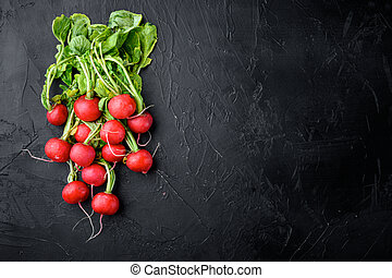 Bunch of radishes. Freshly harvested, purple colorful radish. Growing radish. Growing vegetables. Healthy food background, on black stone background, top view flat lay, with copy space for text