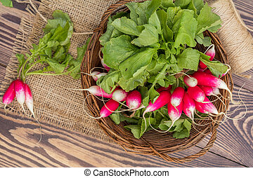 Bunch of radishes in a wicker basket on the table