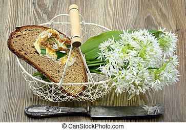 Bunch of ramson wild garlic flower heads and leaves on basket with fresh bread