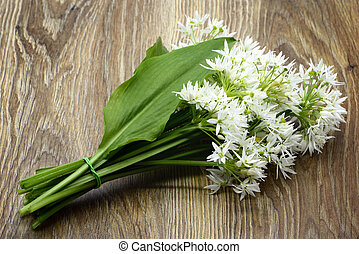 Bunch of ramson wild garlic flower heads and leaves on wooden table