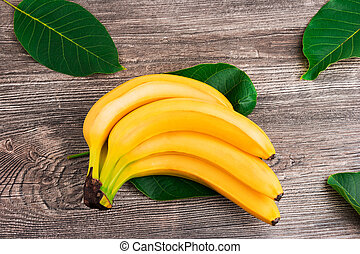 Bunch of raw organic yellow bananas with green leaves on wooden background