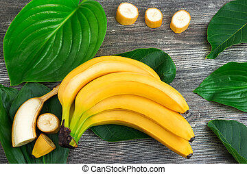 Bunch of raw organic yellow bananas with slices and green leaves on wooden background