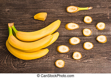 Bunch of raw organic yellow bananas with slices on wooden background