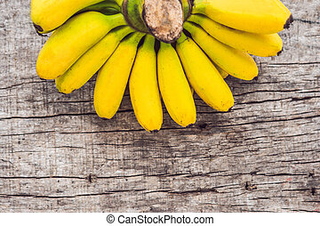 Bunch of raw ripe organic yellow bananas on wooden background