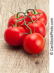 Bunch of red tomatoes on rustic wooden table