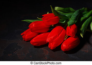Bunch of red tulips on a dark background.