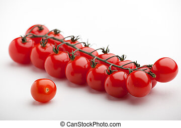 Bunch of ripe red cherry tomatoes close-up on white...
