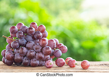 Bunch of ripe red grapes on wooden table with green space blur