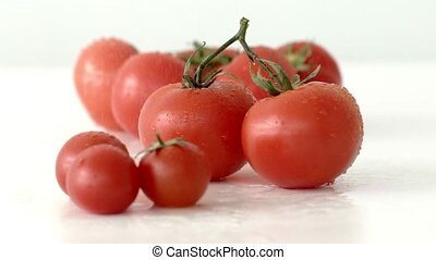 Bunch of ripe tomatoes lies on a mirror surface and being...