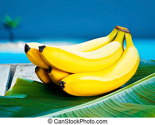 Bunch of ripe yellow bananas nestling on a banana frond under a blue tropical sky