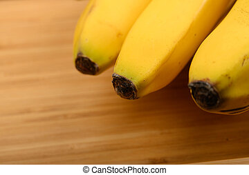 Bunch of ripe yellow bananas on a wooden background. Close up.