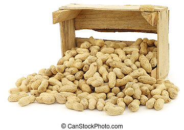 bunch of roasted peanuts in a wooden box on a white...