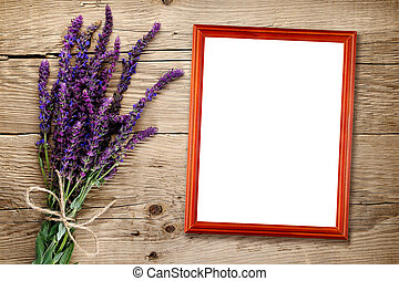 Bunch of salvia and empty photo frame on wooden background