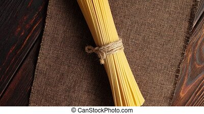 Bunch of spaghetti on burlap textile - From above of tied...