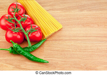 Bunch of spaghetti pasta, green hot peppers and Ripe tomatoes on